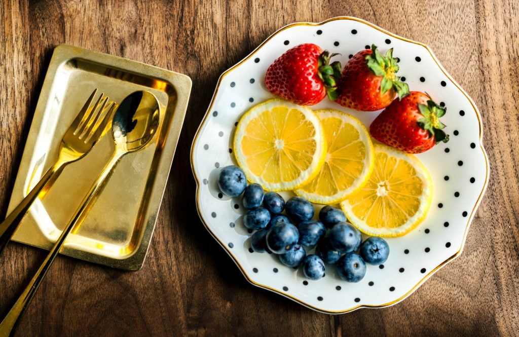 Utensils for eating on top of a metal container with a plate of fruits.