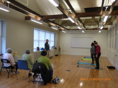 Mr. Kramer teaching qigong energy healing techniques to a class, while other people are sitting watching.